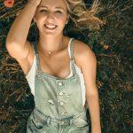 Frau in Latzhose liegt im Gras