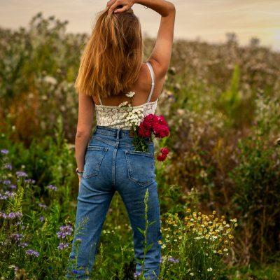 Frau mit Blumen in der Tasche vor Feld