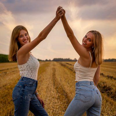 Frauen vor Feld halten die Hände hoch