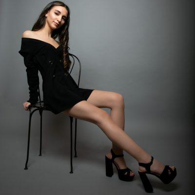 Frau mit langen Beinen sitzt auf Stuhl