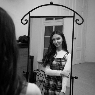 Frau steht vor Spiegel