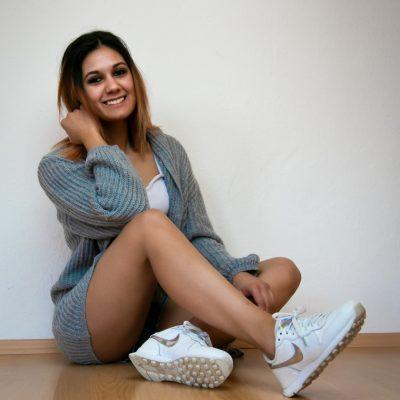 Frau in Pullover sitzt vor Wand