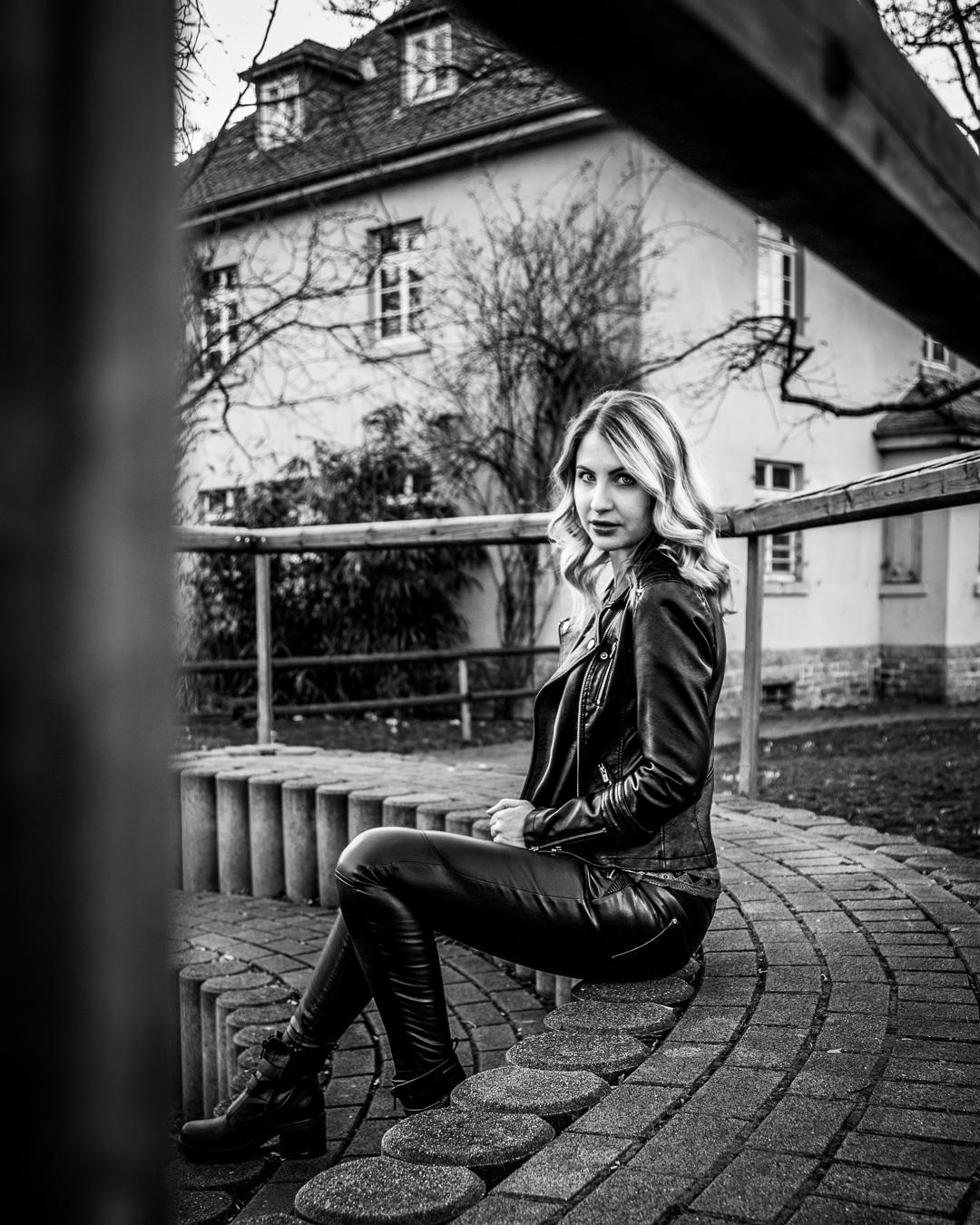 Frau in Lederjacke und Lederhose sitzt