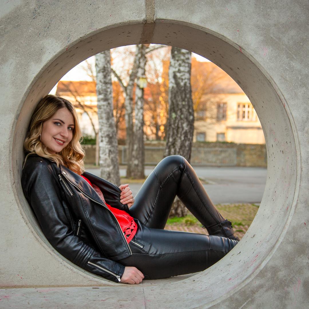 Frau in Lederjacke sitzt in rundem Betondenkmal