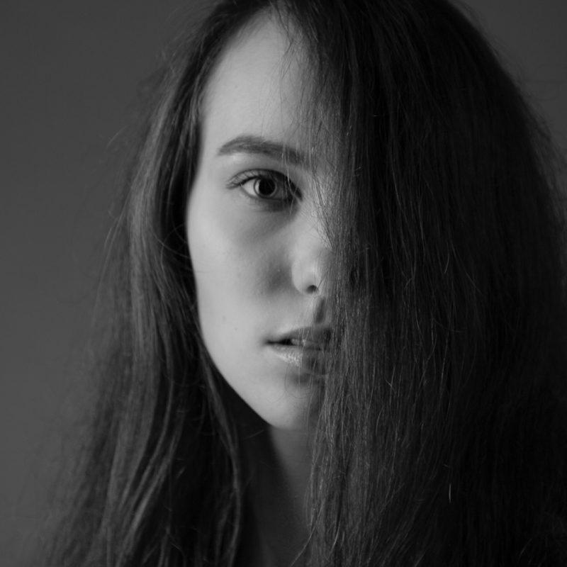 Frau bei der die Haare eine Gesichtshälfte verdecken