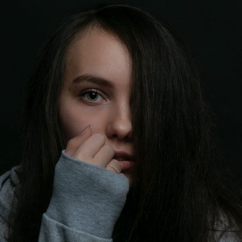 Frau bei der Haare eine Gesichtshälfte verdecken