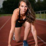 Frau auf Sportplatz in Startposition
