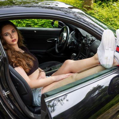 Frau im Auto mit Füßen auf der Tür