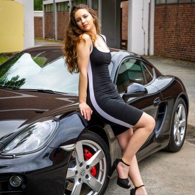Frau in Kleid lehnt an Porsche