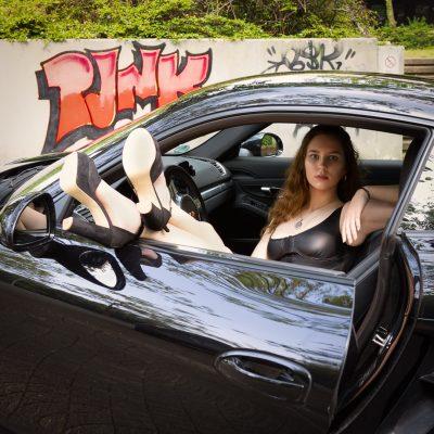 Frau im Auto mit Füßen aus Fenster
