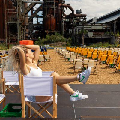 Frau vor Bühne auf Stuhl