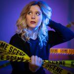 blonde Frau hält Crime Scene Absperrband
