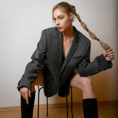 Frau sitzt auf Stuhl und hält ihren Zopf