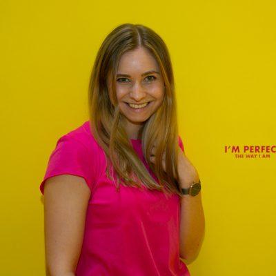 Frau vor gelber Wand mit Spruch