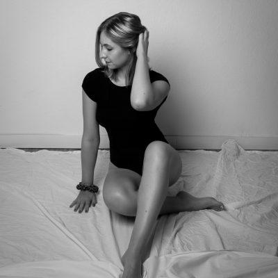 Frau in schwarzem Body sitzt auf Laken