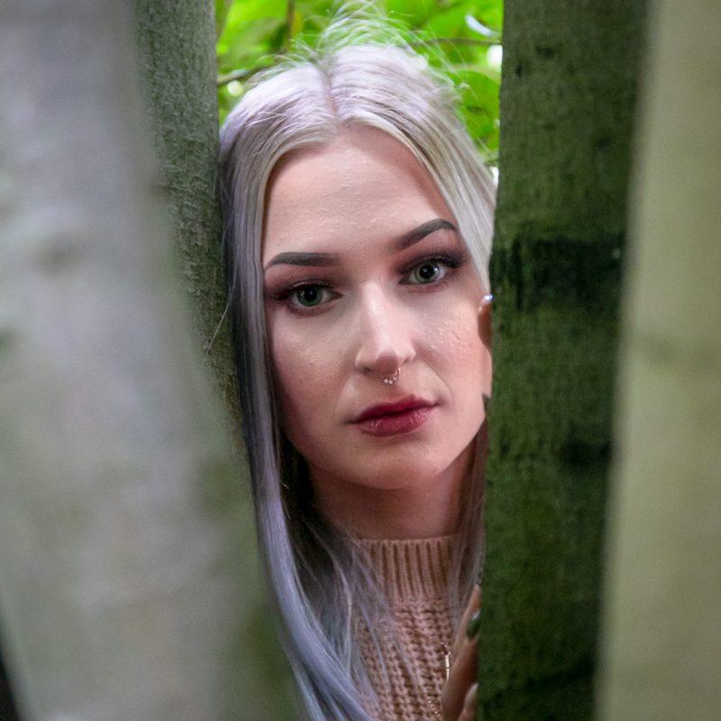 Frau schaut zwischen Bäumen hindurch