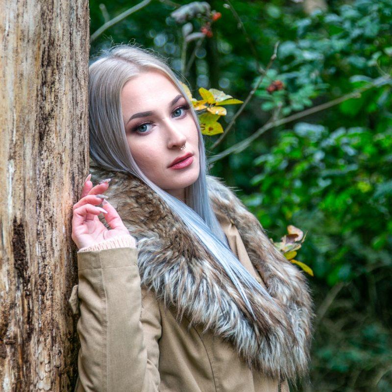 Frau lehnt an Baum