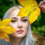 Frau hält Blätter vor das Gesicht