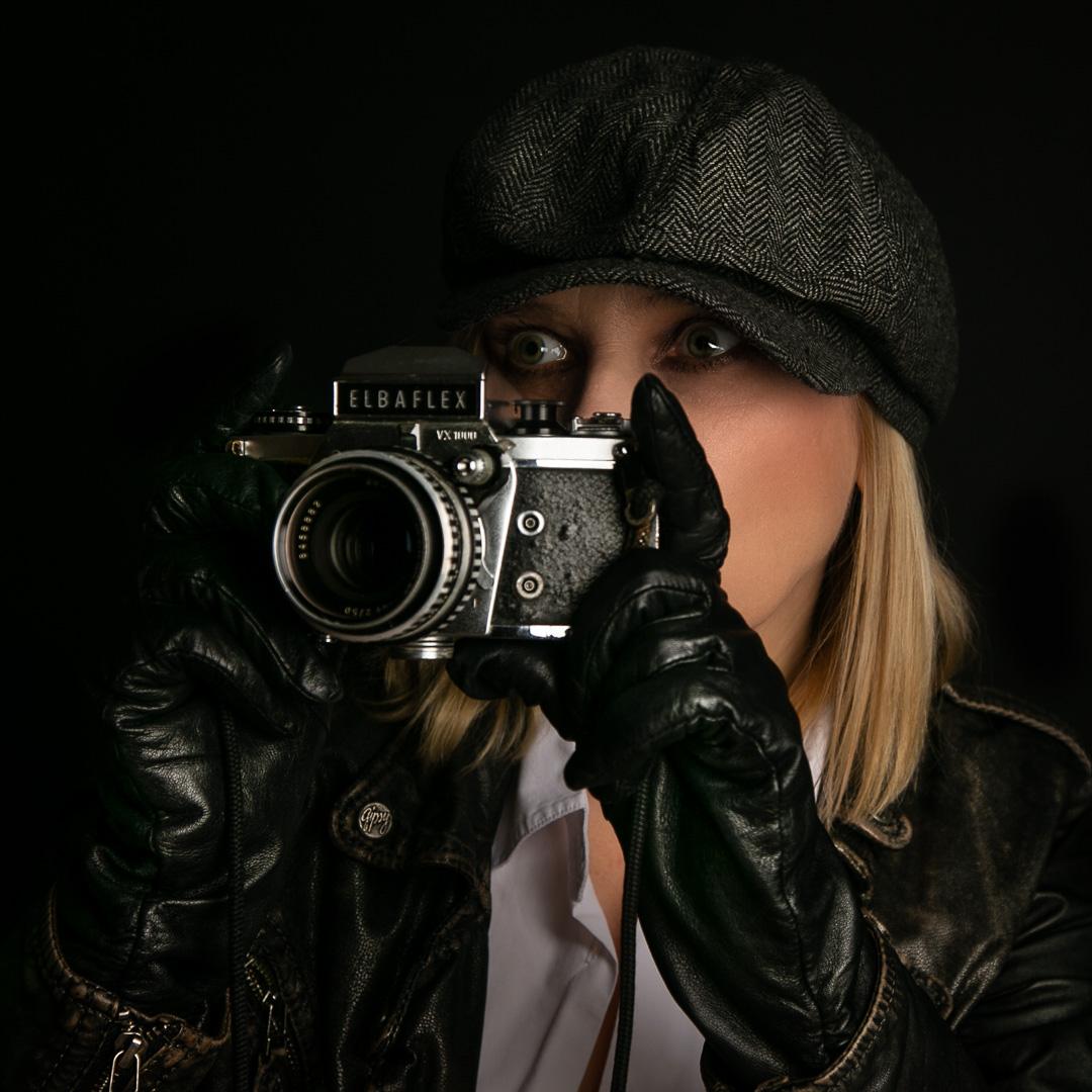 Frau mit alter Kamera im Detektiv Stil