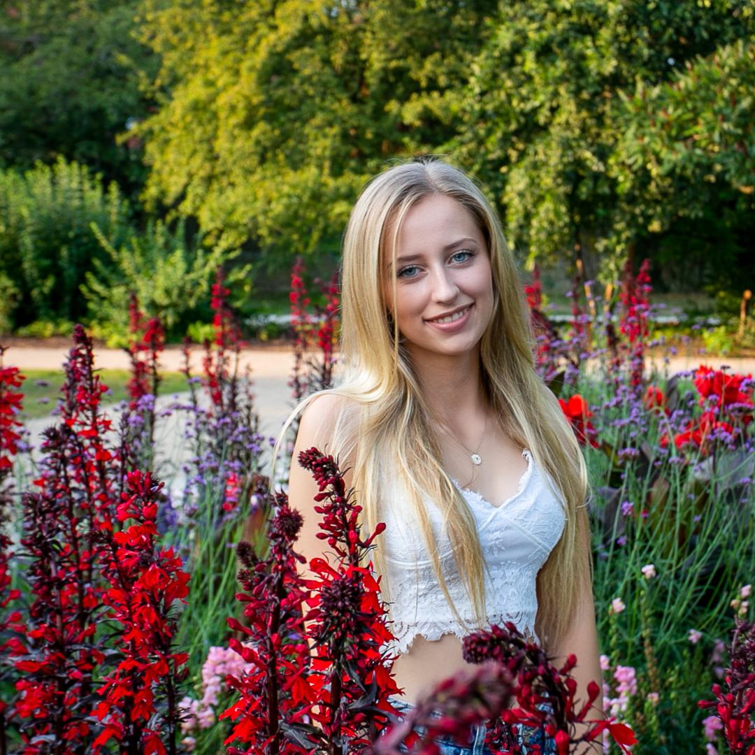 Frau mit blonden Haaren zwischen Blumen