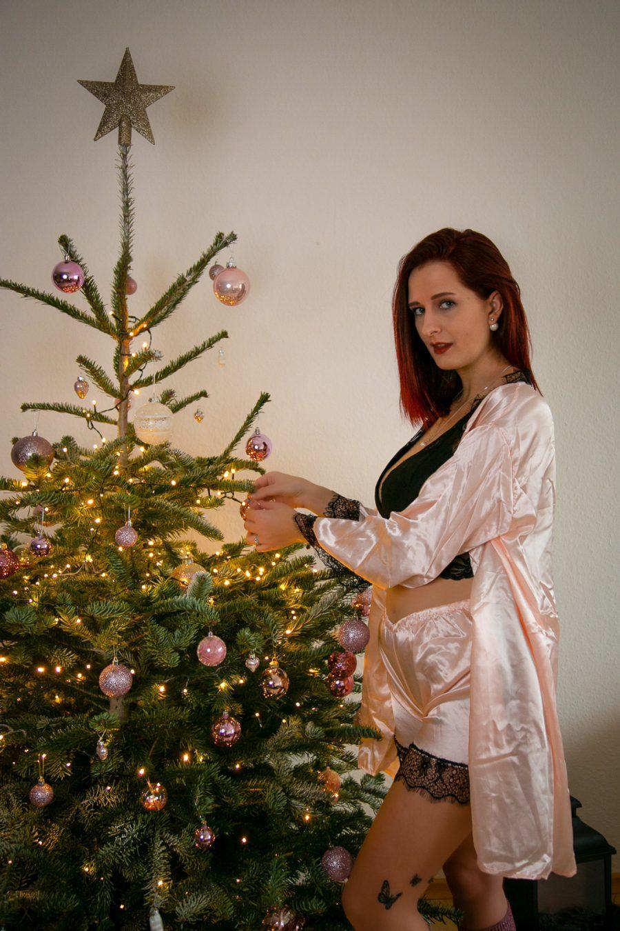 Frau schmückt Weihnachtsbaum