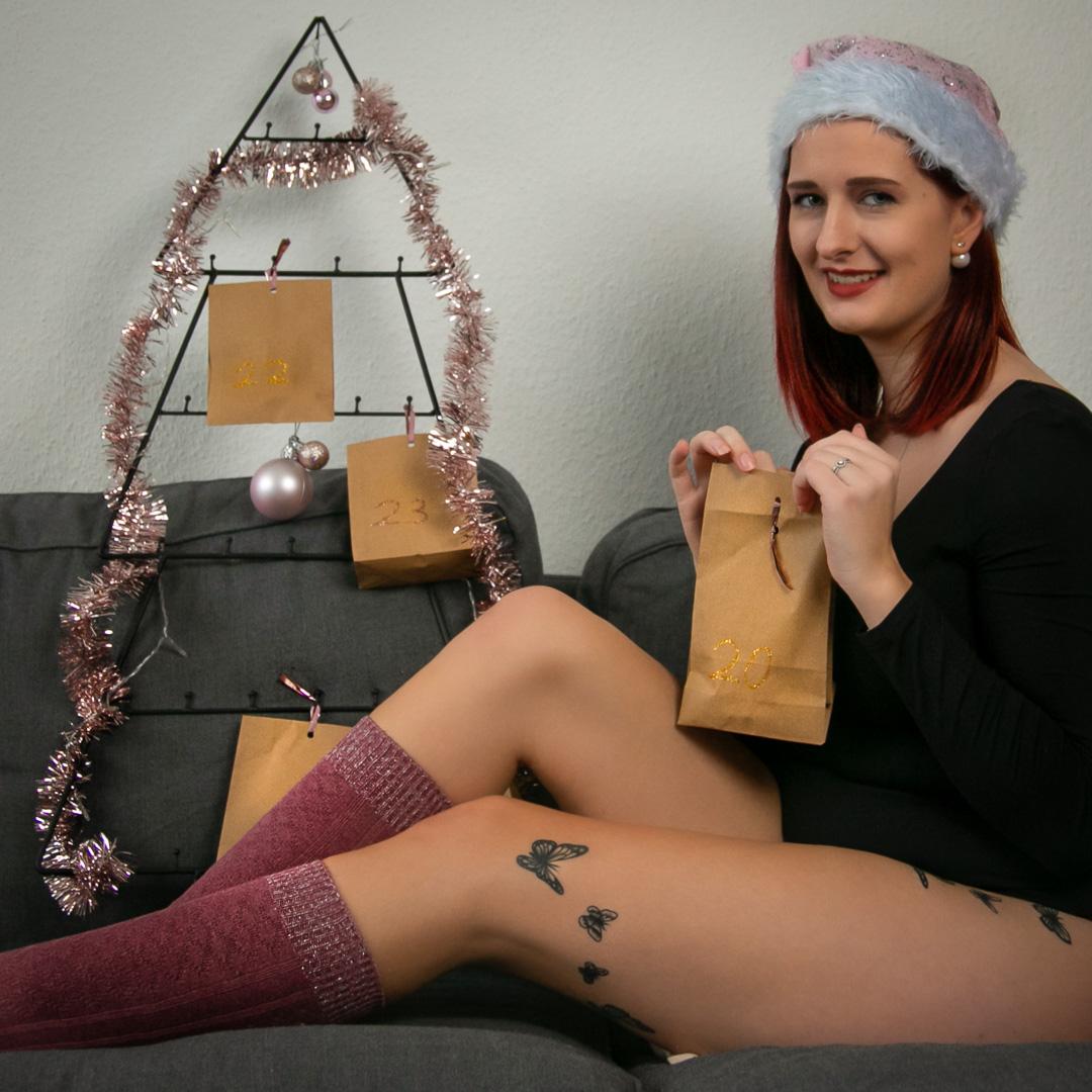 Frau mit Weihnachtsmann Mütze auf Sofa