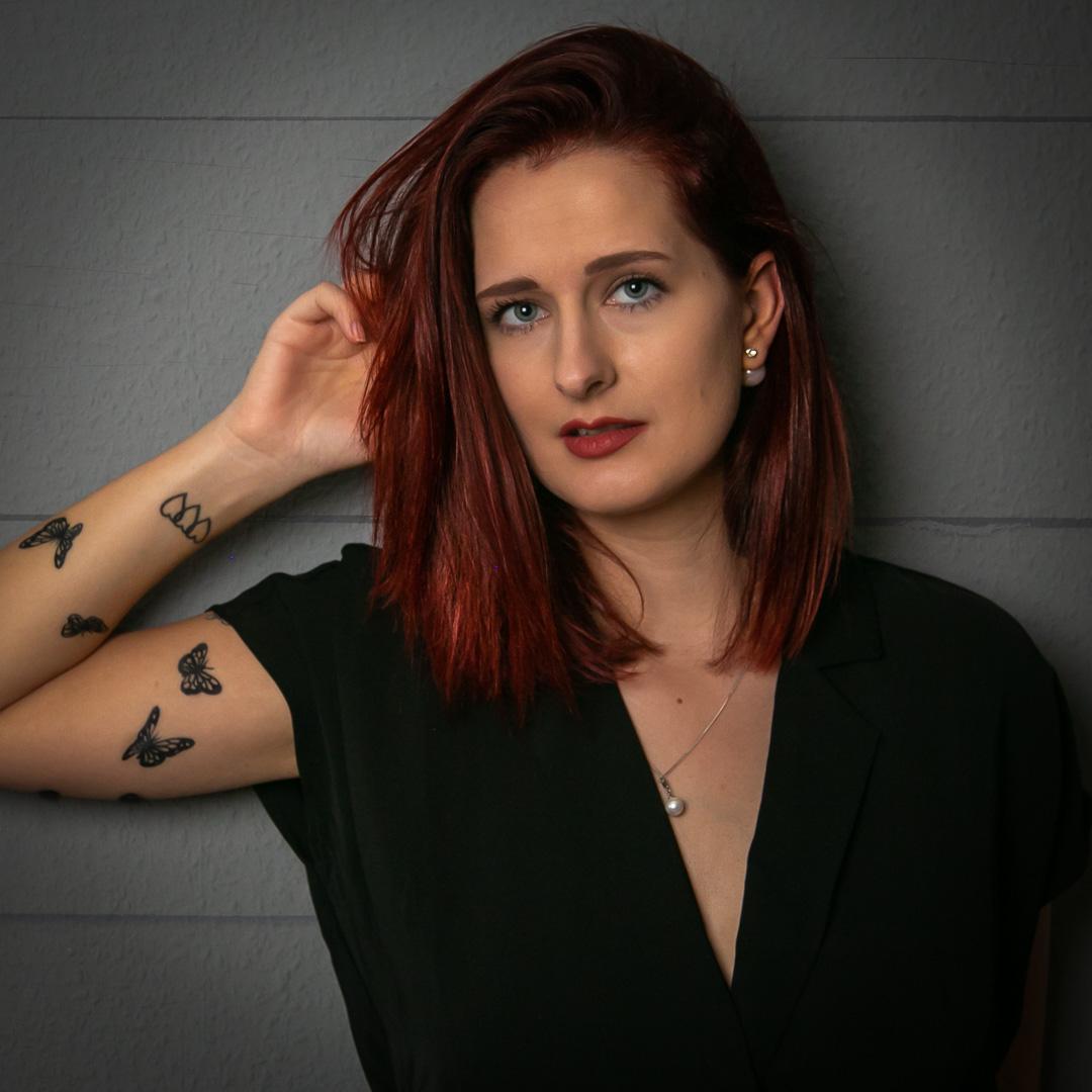 Frau mit roten Haaren vor grauer Wand