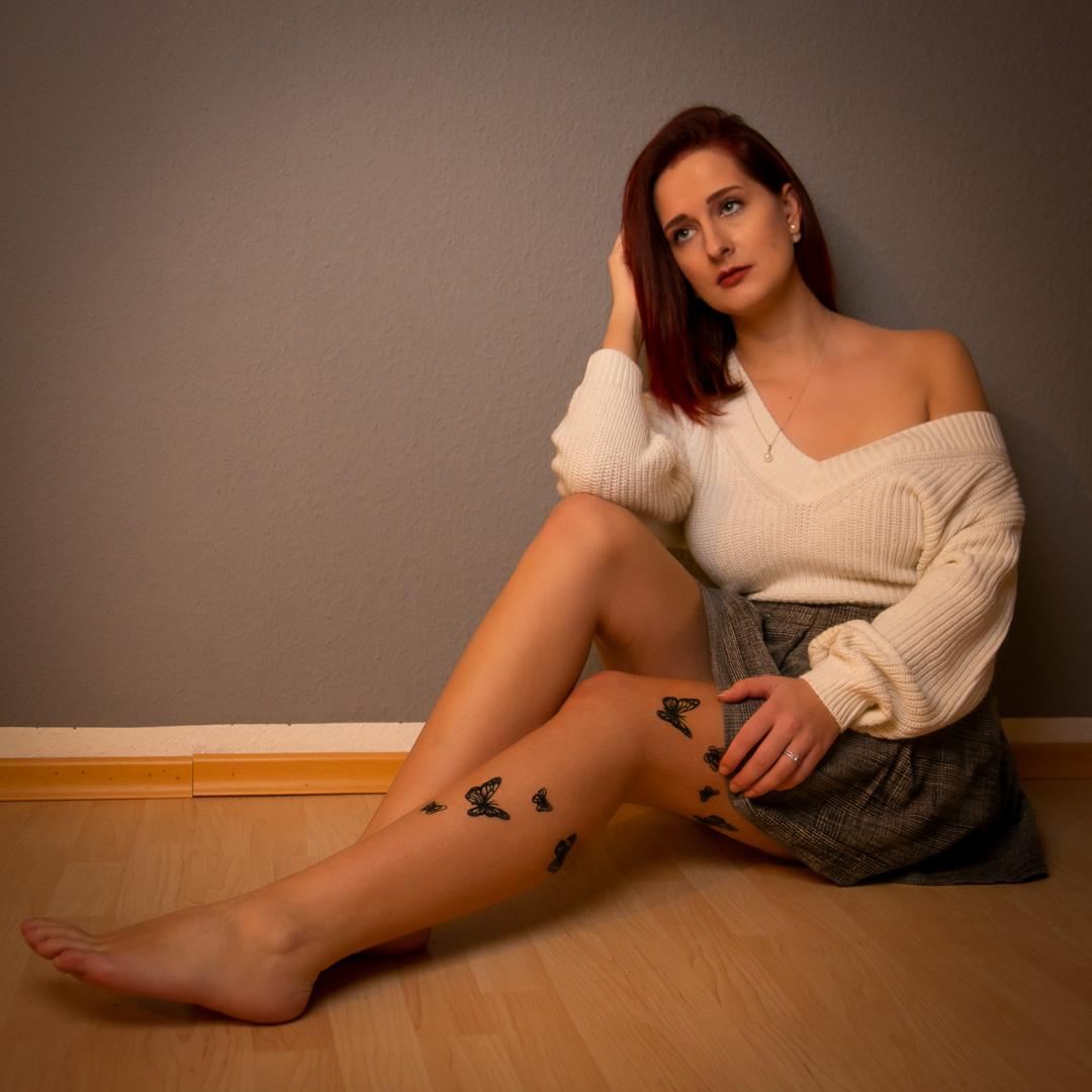 Frau mit Schmetterlings Tatto an den den Beinen sitzt