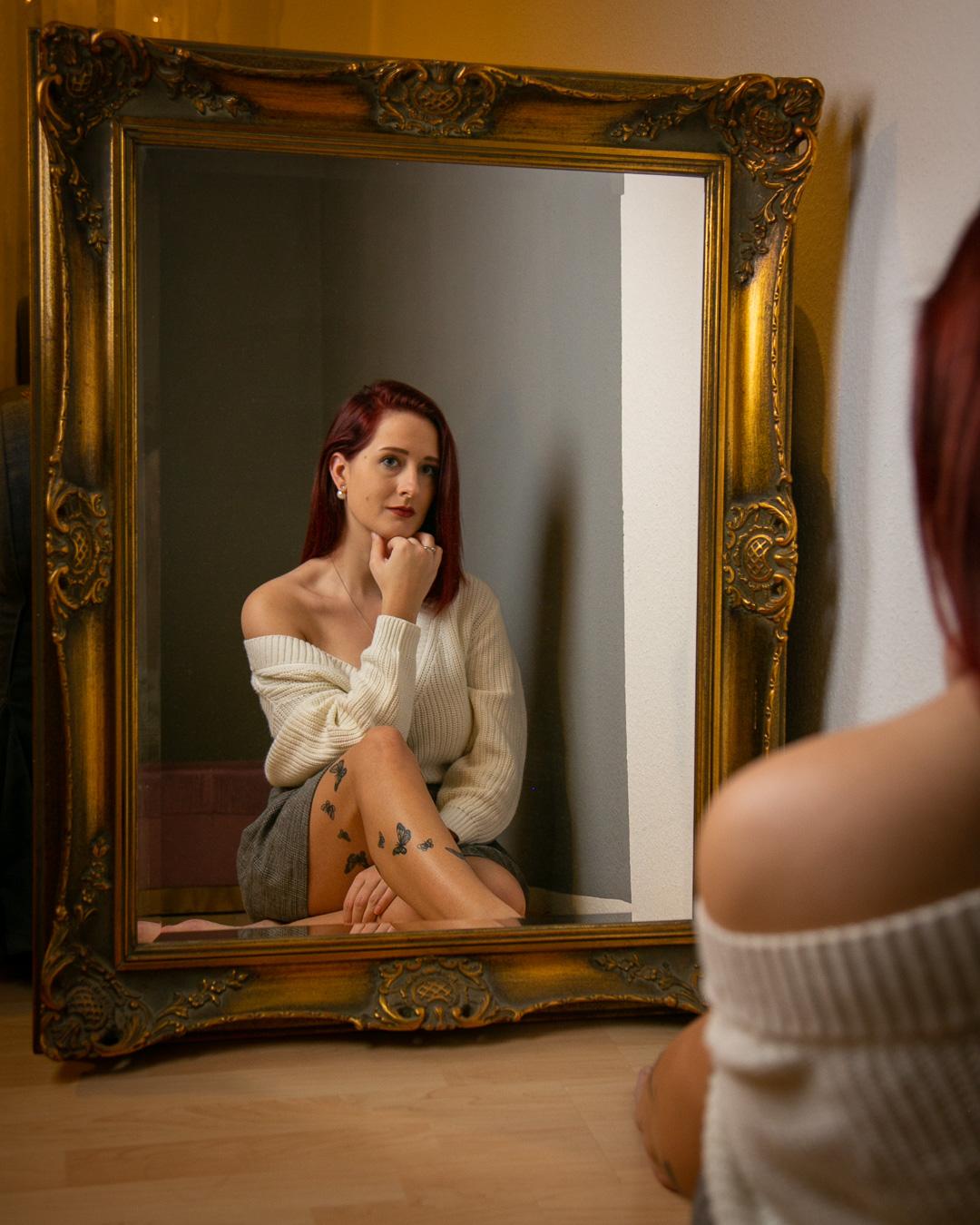 Frau sitzt vor einem Spiegel