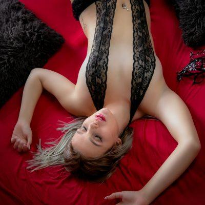 Frau in schwarzen Dessous auf Bett