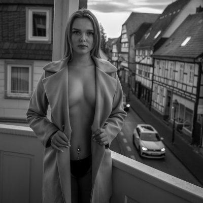 Frau mit offener Jacke auf Balkon
