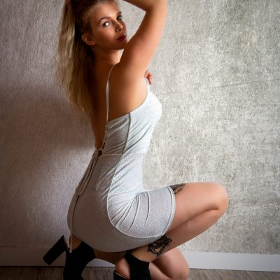 Frau hockt vor Wand