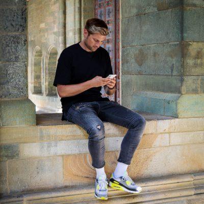Mann mit Handy sitzend