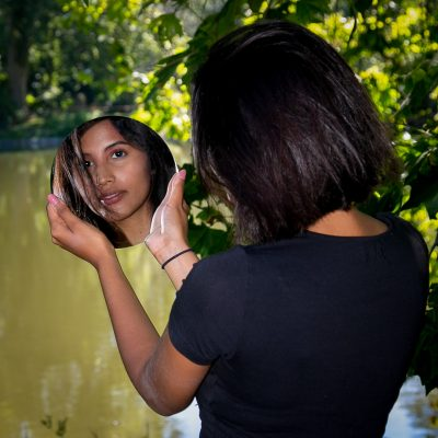 Frau mit Spiegel vor See