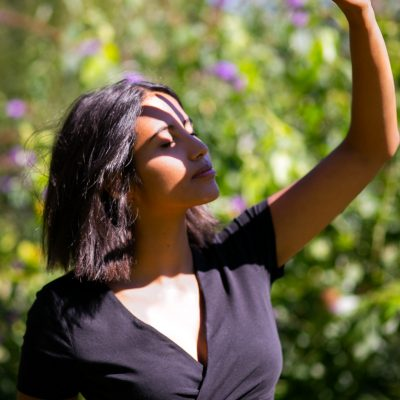 Frau hält Hand in die Sonne