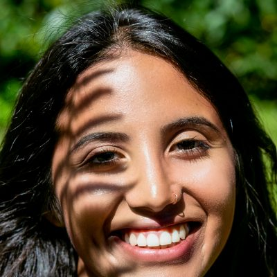 Frau lächelt mit Farn Schatten im Gesicht