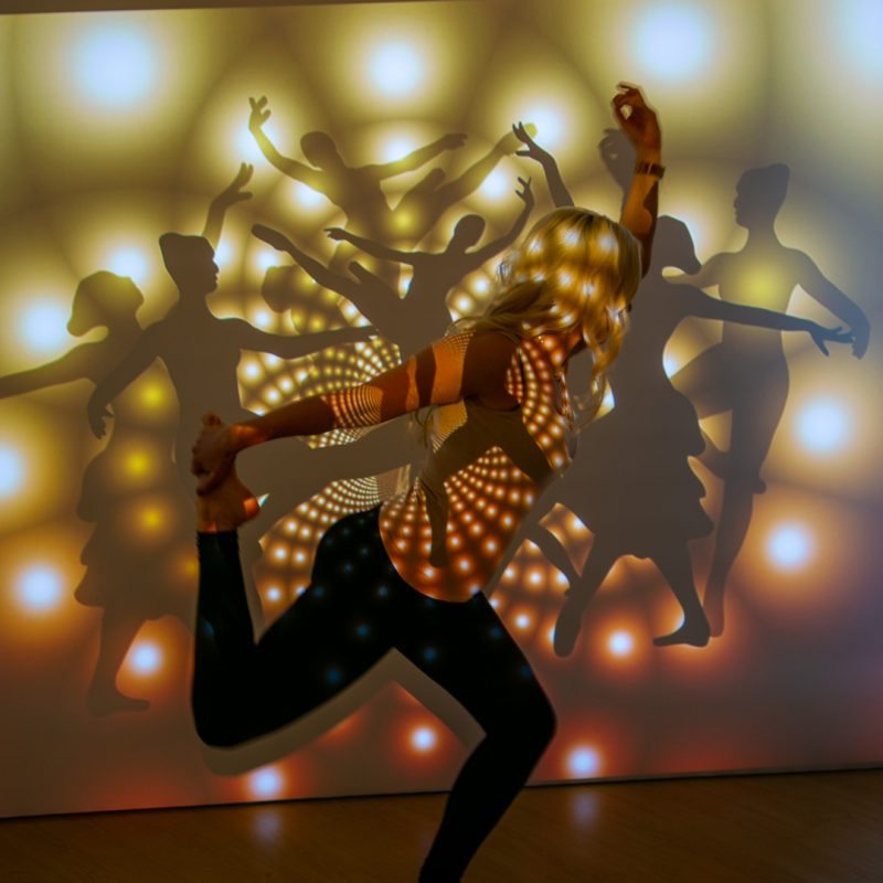 Frau tanzt vor Beamer